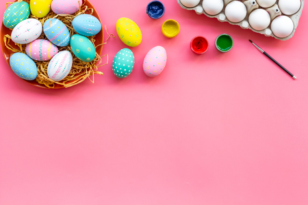 Paint eggs for Easter traditional celebration on pink background top view mock up