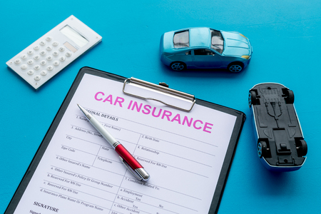 Car insurance concept with form, car toy and calculator on blue desk background