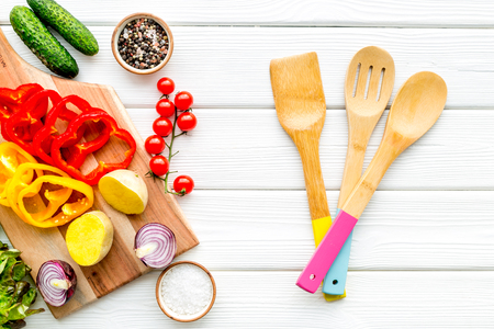 Fresh food with raw vegetable ingredients for vegetarian kitchen on white wooden background top view