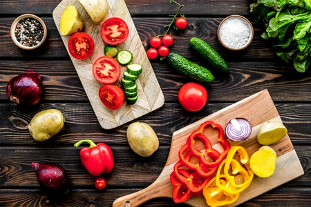 Fresh food with raw vegetable ingredients for vegetarian kitchen on wooden background top view