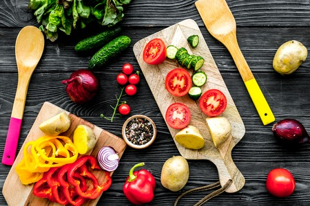 Vegan food cooking with raw vegetables on black wooden table background top view