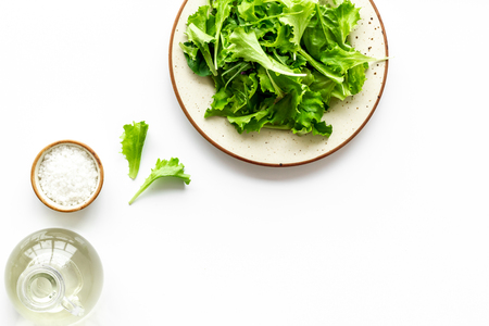 Organic food pattern with green salads mix and oil on white background top view space for text Stock Photo