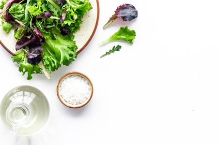 Organic food pattern with green and red salads mix and oil on white background top view space for text Stock Photo