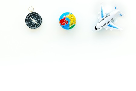SOS Save the planet concept with the earth, plane and compass on white background top view flat lay space for text.