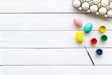 Eggs with colorful paint for Easter tradition on white wooden table background top view mockup Stock Photo