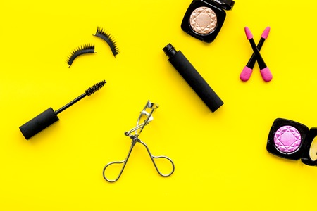 Female desk with decorative cosmetic for make up on yellow background top view Stock Photo