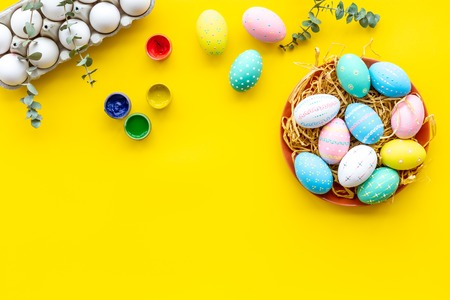 Paint eggs for Easter traditional celebration on yellow background top view mock up