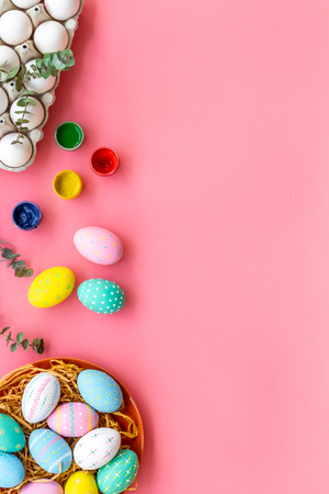 Colorful Easter eggs and paint for celebration on pink table background top view mock up