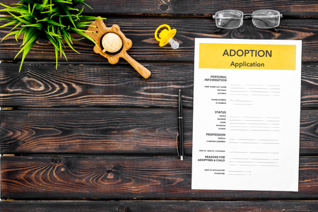 Adoption children concept with form and dummy for baby on wooden table background top view mock up