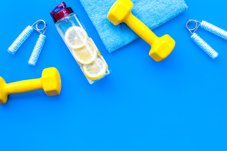 Sport with bars, towel, water and wrist builder on blue background top view space for text.