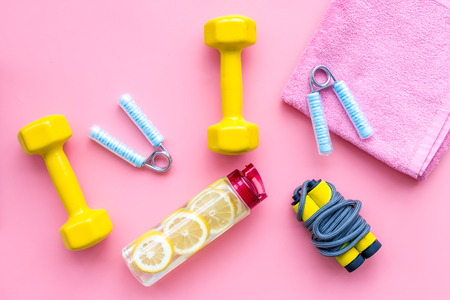 Fitness background with sport equipment for gym and home workout on pink background top view