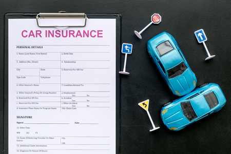 Car insurance concept with form, car toys on black desk background top view Stock fotó