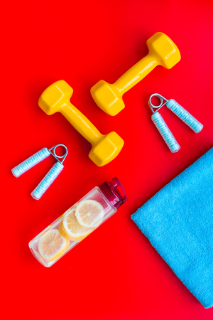 Sport with bars, towel, water and wrist builder on red background top view