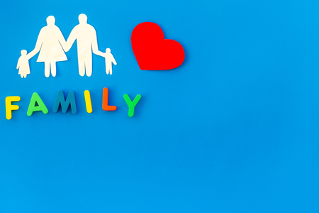 Family copy and figures on blue table background top view copyspace