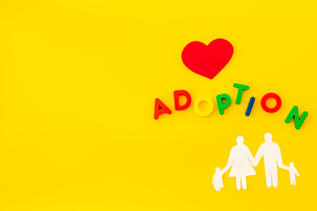 Adoption copy and figures on yellow table background top view copyspace