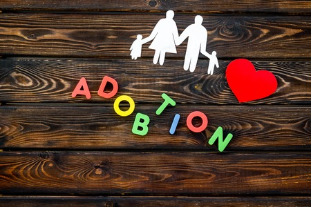 Adoption copy and figures on wooden table background top view Stock Photo