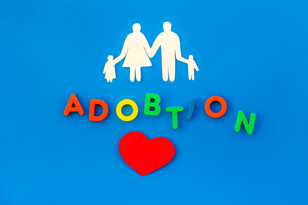 Adoption copy and figures on blue table background top view