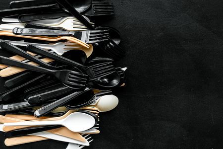 Plastic utilization and the Earth protection concept with flatware on black background top view mock up