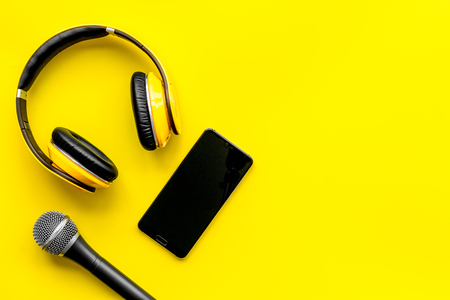 Blogger, journalist or musician office desk with mobile phone, microphone and headphones on yellow background top view copyspace
