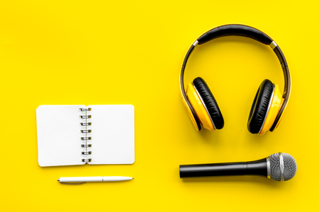 Blogger, journalist or musician office desk with notebook, microphone and headphones on yellow background top view copyspace Stock Photo
