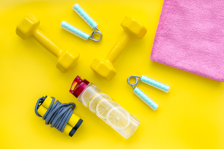 Fitness set with bars, towel, bottle of water and wrist builder on yellow background top view