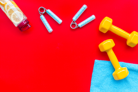 Workout with bars, bottle of water and wrist builder red background top view mockup