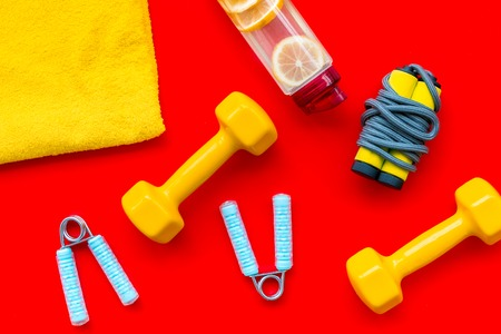 Fitness set with bars, towel, bottle of water and wrist builder on red background top view