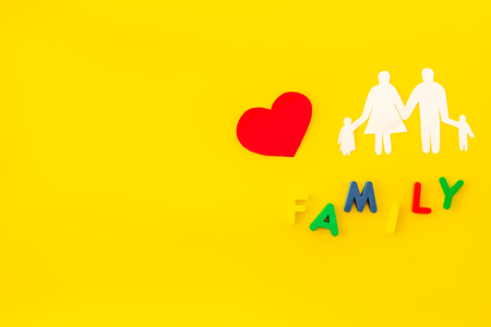 Paper figure for adoption concept with family copy on yellow background top view space for text