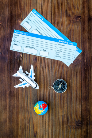 SOS Save the planet and ecology concept with the earth, compass, tickets and plane on dark wooden background top view.