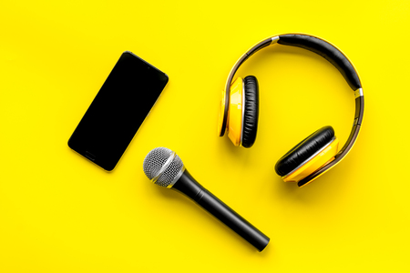 Podcast record with mobile phone, microphone and headphones on yellow office desk background top view space for text