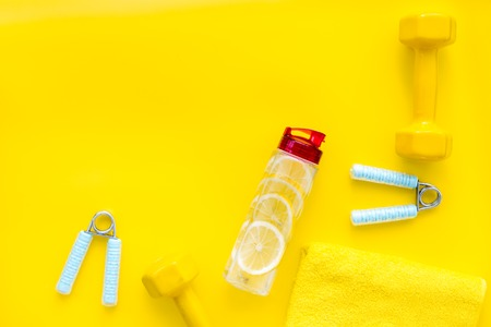Workout with bars, bottle of water and wrist builder on yellow background top view mockup 写真素材