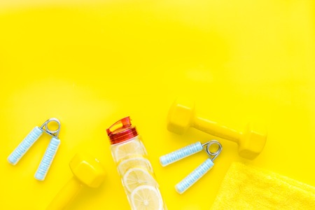 Fitness set with bars, towel, bottle of lemon water and wrist builder on yellow background top view mock up 写真素材
