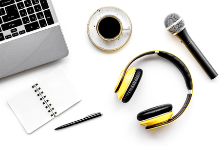Podcast record with laptop, coffee, notebook, microphone and headphones on white office desk background top view space for text