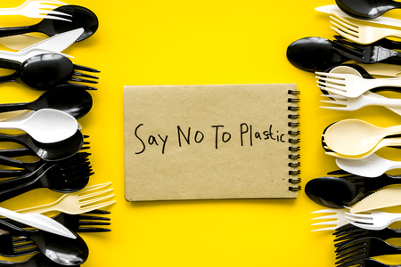 Say no to plastic copy. Eco concept and injunction on the use of plastic flatware on yellow background top view