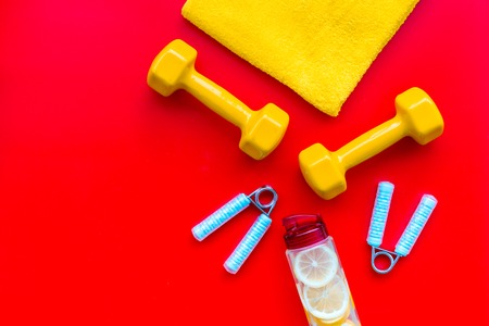 Sport with bars, towel, water and wrist builder on red background top view space for text