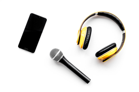 Podcast record with mobile phone, microphone and headphones on white office desk background top view space for text
