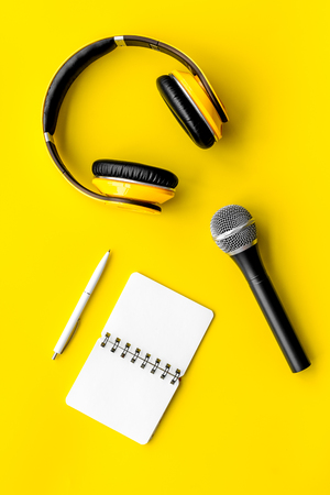 Podcast record with notebook, microphone and headphones on yellow office desk background top view space for text