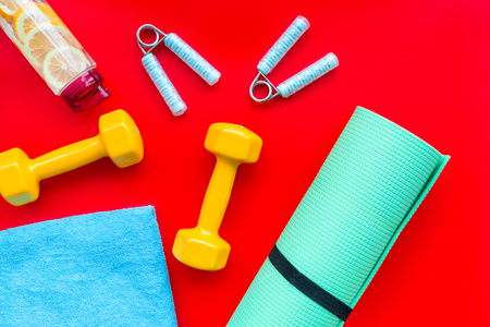 Fitness background with sport equipment for gym and home workout on red background top view 写真素材