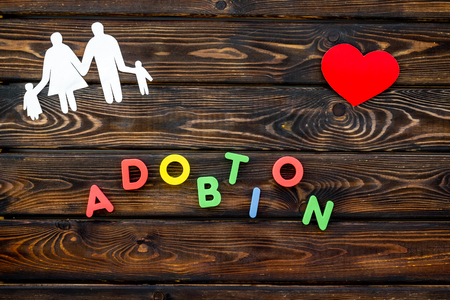 Family figure with adoption copy on wooden background top view