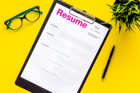 Review resumes of applicants set with glasses on yellow work desk background top view Stock Photo
