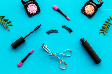 Organic decorative cosmetic set with lash curler and mascara on blue woman desk background top view. 写真素材