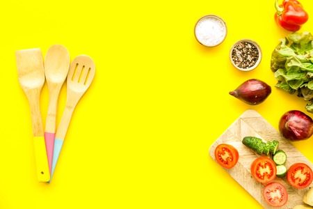 Cooking with raw vegetables on yellow kitchen background top view
