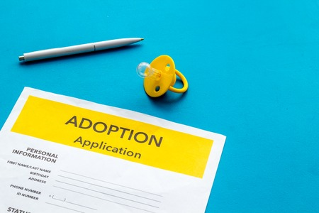 Children care with adoption application and dummy on blue office table background