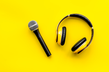 Podcast record with microphone and headphones on yellow background top view Stock Photo