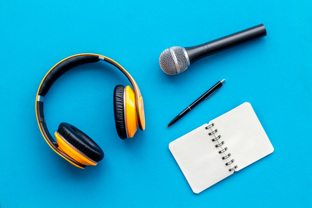 Blogger, journalist or musician office desk with notebook, microphone and headphones on blue background top view copyspace Stock Photo