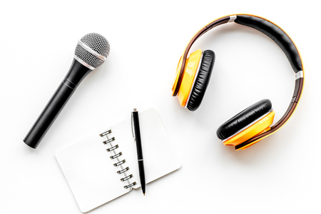 Blogger, journalist or musician office desk with notebook, microphone and headphones on white background top view copyspace Stock Photo