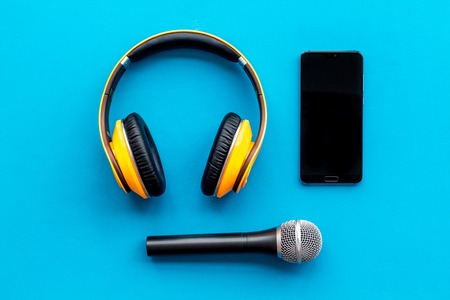 Blogger, journalist or musician office desk with mobile phone, microphone and headphones on blue background top view copyspace