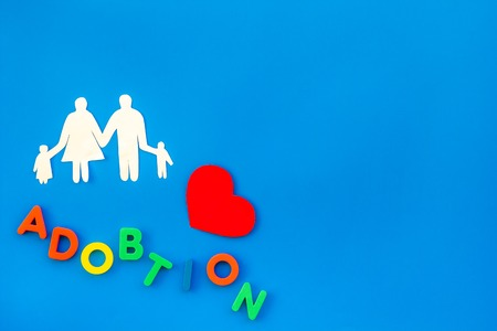 Adoption word and family figure for adopt child concept on blue table background top view mock up