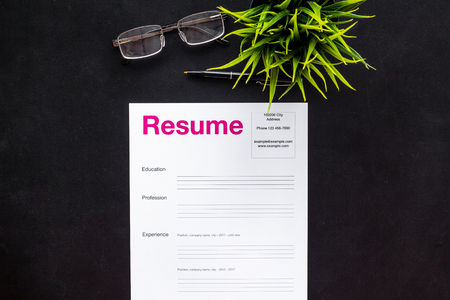 Review resumes of applicants set with glasses on black work desk background top view