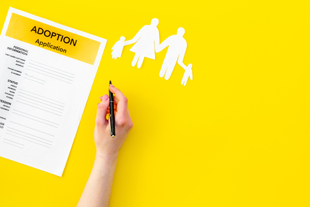 Application form for adopt child on yellow table background top view mock up